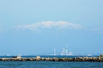 富山新港の火力発電所と、建設中の大橋を抱き抱えてるみたいに、大きな薬師岳です。