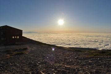 見事な雲海と夕日。遠くに加賀の白山を望む。
